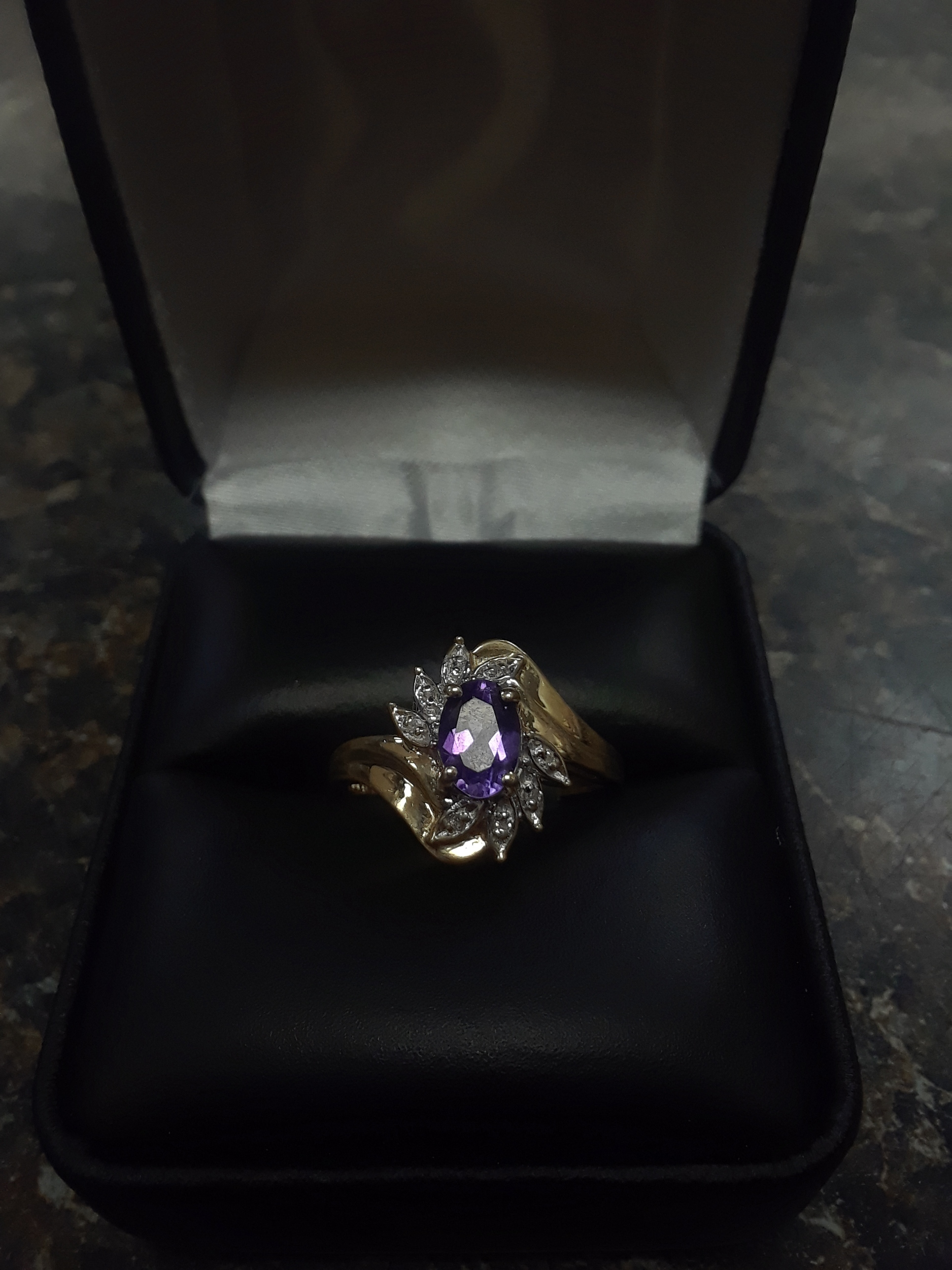 10KT YELLOW GOLD RING WITH A PURPLE OVAL STONE SURROUNDED BY TINY DIAMOND CHIPS. SIZE: 7